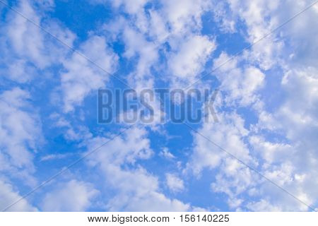 Background with clouds in the blue sky. Texture atmospheric sky high. Feathery white clouds.