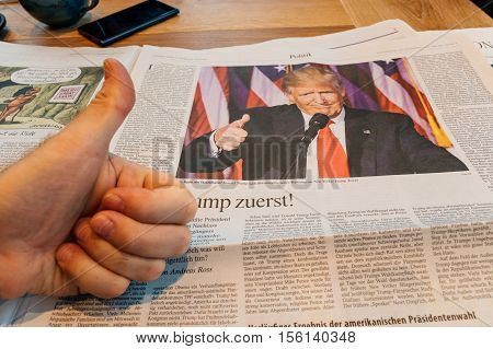 FRANKFURT GERMANY - NOV 10 2016: Thumb up for Donald Trump - Man reading The Economist magazine with Donald Trump and Hillary Clinton after US President Election - Donald Trump is the 45th President of United States of America