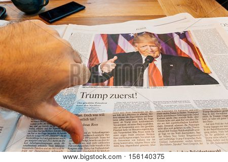 FRANKFURT, GERMANY - NOV 10 2016: Thumb down for Donald Trump - Man reading The Economist magazine with Donald Trump and Hillary Clinton after US President Election - Donald Trump is the 45th President of United States of America