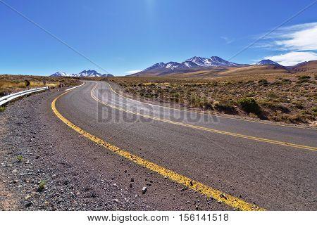 Desert asphalt road crossing desert mountainous landscape.