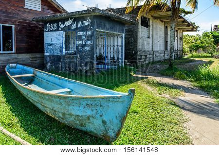 Livingston, Guatemala - August 31 2016: Boat sits on grass outside beachside building in Caribbean town of Livingston Guatemala. Wording on wall reads