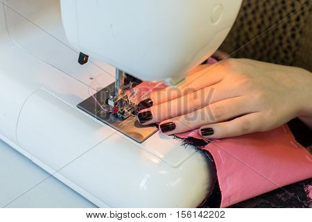 Sewing machine foot on material with threaded needle ready to sew. Operator's hand on material in top left corner.