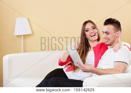 modern technologies leisure and relationships concept. Young couple with pc computer tablet sitting on couch at home websurfing on internet