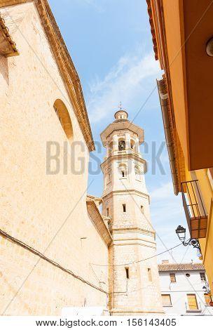 Alcalali church spire rising through narrow typically historic Mediterranean village street Spain.