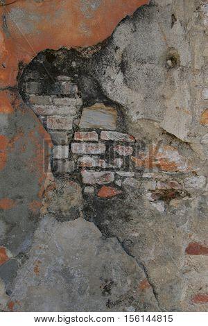 Rough textured cracked plaster on brick photo background