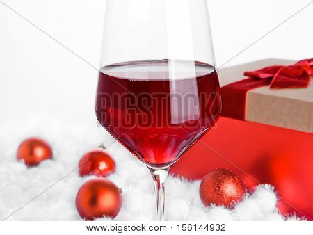 Glass of red wine on snow with christmas balls on white background