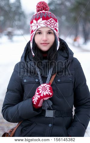Adorable girl wearing warm clothes outdoors on beautiful winter snow day.Young Woman having fun in winter park in Snowy Weather.A woman dressed for winter pulls her drawstrings down and smiles