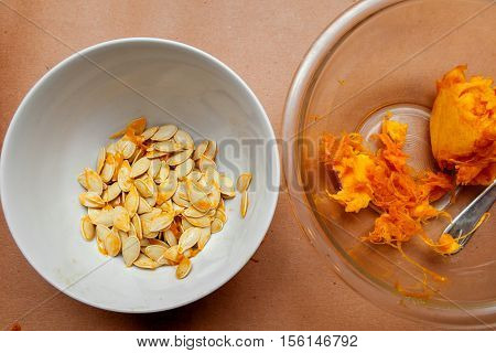 Two bowls containing the insides of a pumpkin. One with seeds one with pulp.