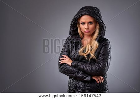 A beautiful young woman standing in a winter jacket and feeling upset
