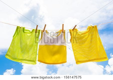 Baby clothes laundry hanging on the clotheline for sun dry after wash over blue sky in sunny day