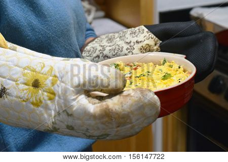 Woman holding casserole dish of Mexican cheese dip with oven mitts