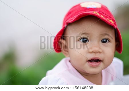 Cute little baby girl with red hat on nature background