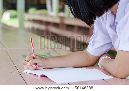 Close up of young student hands writing on notebook