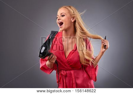 A beautiful happy young woman wearing a pink robe and and singing while using a hairdryer and a hairbrush