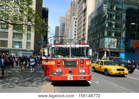 NEW YORK CITY - MAY 7: Red Fire Truck on duty at Fifth Avenue in Manhattan on May 7th, 2013 in New York City, USA.