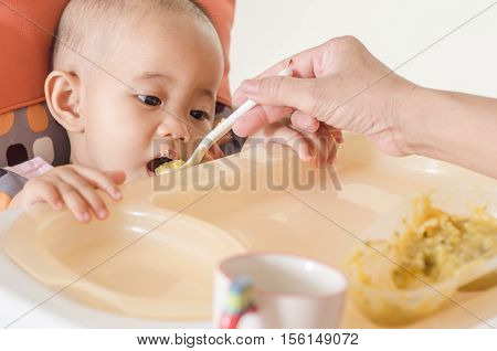 Closeup of mother feeding asian baby girl with a spoon in high chair