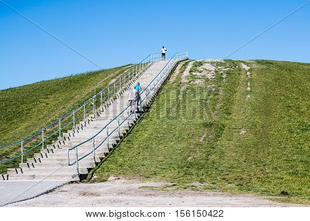 VIRGINIA BEACH, VIRGINIA - MAY 2, 2015: People exercise on the steep stairway in the springtime at Mount Trashmore Park, the site of a former landfill.