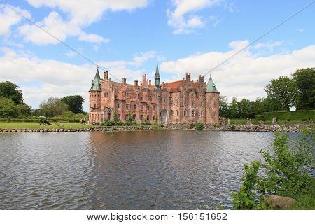FUNEN, DENMARK - JUNE 4, 2010: Egeskov castle and lake on June 3, 2010 in Funen, Denmark. It is a landmark fairy tale castle in Denmark.