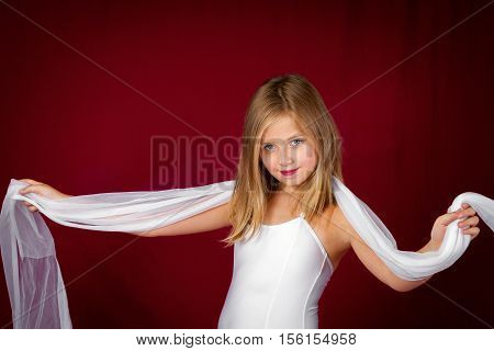 A young girl in a ballet leotard holds a white scarf across her shoulders and stares confidently at the camera. She stands in front of a red backdrop.