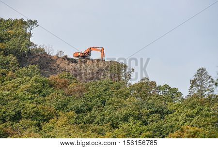Excavator standing on top of gravel hill and moving gravel with scoop