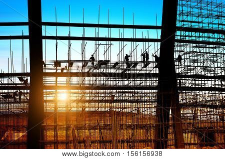 Construction workers working on scaffolding dusk picture.