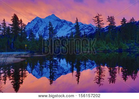 Mountains reflecting in calm waters of lake during sunrise
