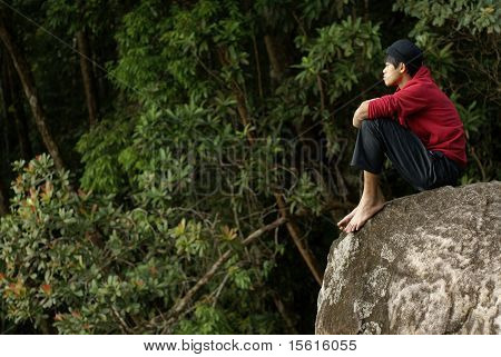 Lonely asian man sitting on rock
