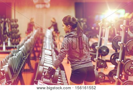 fitness, sport, exercising, weightlifting and people concept - young woman choosing dumbbells in gym