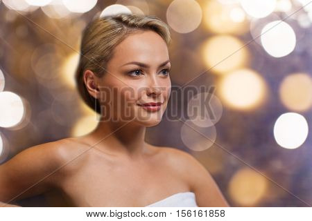 people, beauty, spa, bodycare and relaxation concept - close up of beautiful young woman sitting in bath towel over holidays lights background