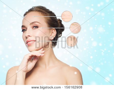 beauty, people, aging, winter and skin concept - beautiful young woman touching her face over blue background and snow