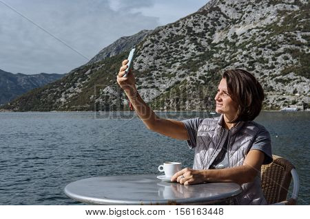 Young Woman Drinking Coffee And Using Smarphone In The Morning At Restaurant Near The Sea (soft Focu