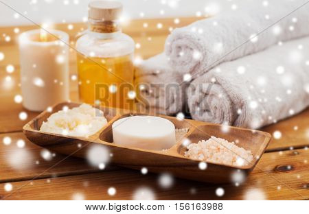 beauty, spa, bodycare, natural cosmetics and bath concept - soap with himalayan salt with scrub in wooden bowl and massage oil on table over snow