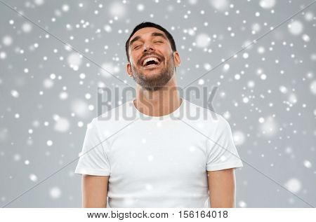 emotion, winter, christmas and people concept - laughing man over snow on gray background