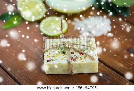 beauty, spa, bodycare, bath and natural cosmetics concept - handmade herbal soap bar on wood over snow
