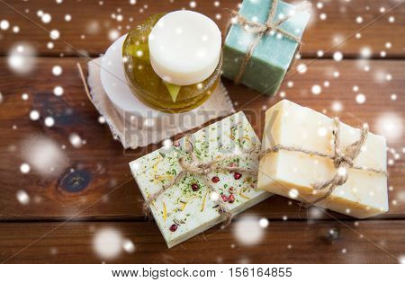 beauty, spa, bodycare, bath and natural cosmetics concept - handmade soap bars on wooden table over snow