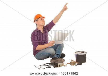 male construction worker with plan in his hands and tools scattered around points finger at something isolated on white background