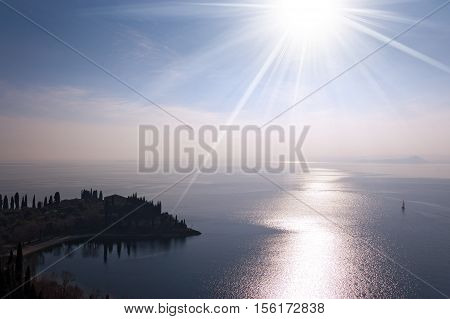 Punta San Vigilio small promontory in the Garda Lake (Lago di Garda) with sun rays (backlight). Italy Europe
