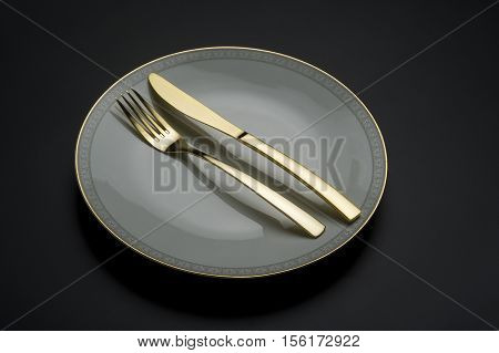 Close up on single fine china plate with knife and fork over dark background for concept about fine dining