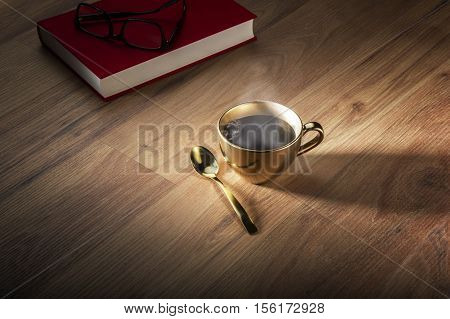 Book and eyeglasses near golden cup of steaming hot tea or coffee for concept about knowledge and wealth