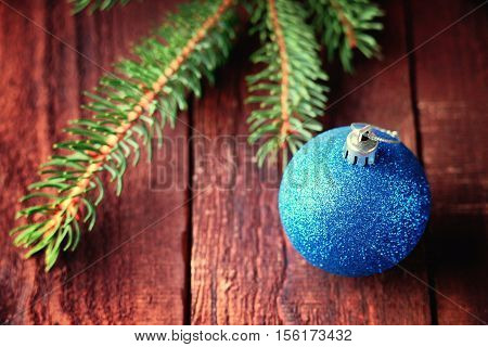 Christmas ball and fir tree branch on a wooden background