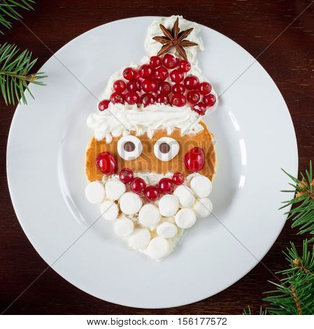 Santa Claus pancake! Creative food art breakfast for kids on Christmas or New Year. Top view, white plate background. Christmas food, New Year food, Kids meal. Square