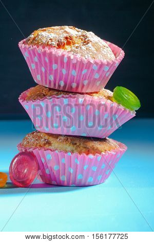 A pyramid of three  muffins or cupcakes on the  table