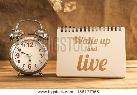 Wake Up And Live Text On Notebook With Alarm Clock On Wood Table.