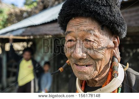 LONGWA, NAGALAND/INDIA - DECEMBER 9, 2013: Tattooed face of elderly former Longwa Village headhunter. Naga tribes practised headhunting & preserved the heads of enemies as trophies.