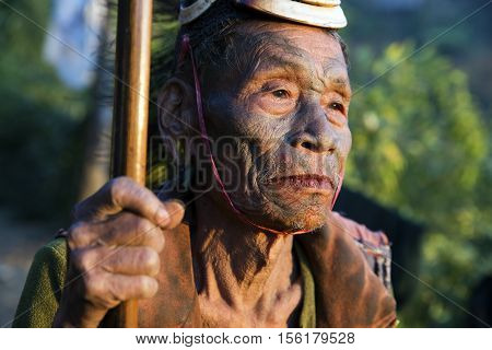 SINGHA CHINGNYU, NAGALAND/INDIA - DECEMBER 8, 2013: Tattooed face of elderly former Singha Chingnyu Village Headhunter. Naga tribes practised headhunting & preserved the heads of enemies as trophies.