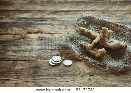 three crust of bread on canvas cloth metal coins on wooden table starvation concept