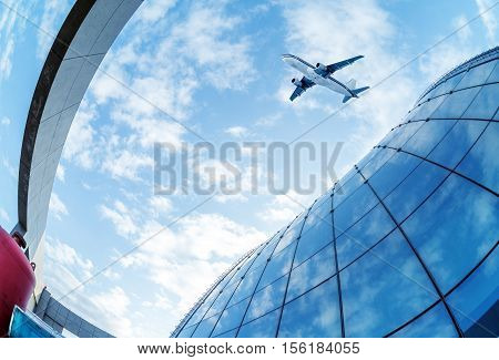 Shot of airplane flying above glass office buildings. Fisheye lens effect.