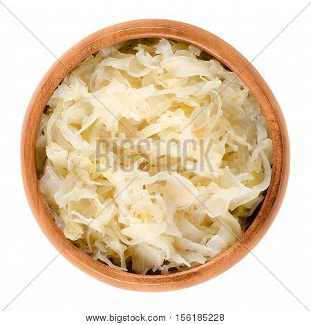 German sauerkraut in wooden bowl over white. Finely cut cabbage, fermented by lactic acid bacteria with long shelf life and distinctive sour flavor, used as a side dish. Isolated macro food photo.