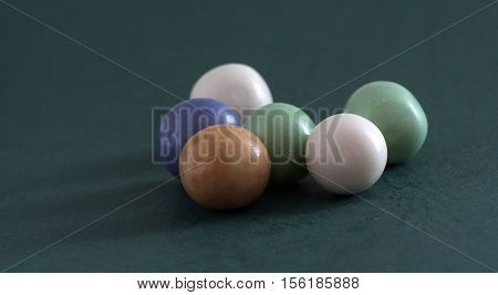 picture of a pile of bubble gum balls on dark green background