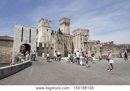 Sirmione, Italy - June 10, 2016: Tourists come into Sirmione through the castle gate